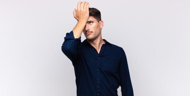Jonge knappe man die de handpalm naar het voorhoofd opheft, denkend oeps, na het maken van een domme fout of het herinneren, zich dom voelen