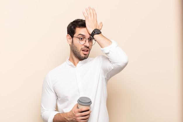 Jonge knappe man die de handpalm naar het voorhoofd steekt en denkt oeps, na een domme fout te hebben gemaakt of zich te herinneren, zich dom te voelen