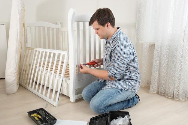 Jonge knappe man die de wieg van de baby in de kinderkamer in elkaar zet