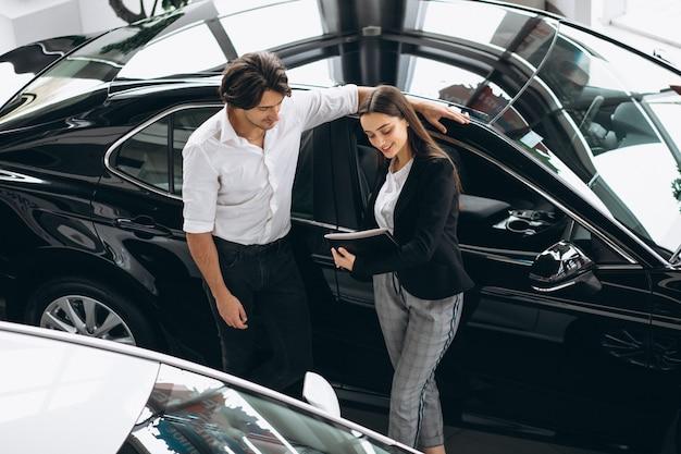 Jonge knappe man die een auto in een autotoonzaal kiest