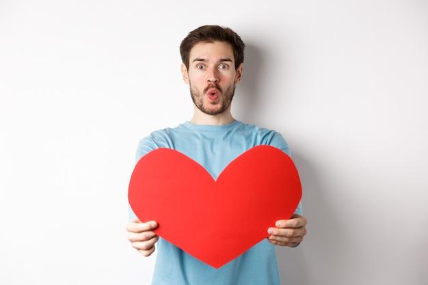 Jonge knappe man die een groot rood valentijnsdaghart toont, verliefd is, lippen tuit voor kus op valentijnsdatum, staande op een witte achtergrond.