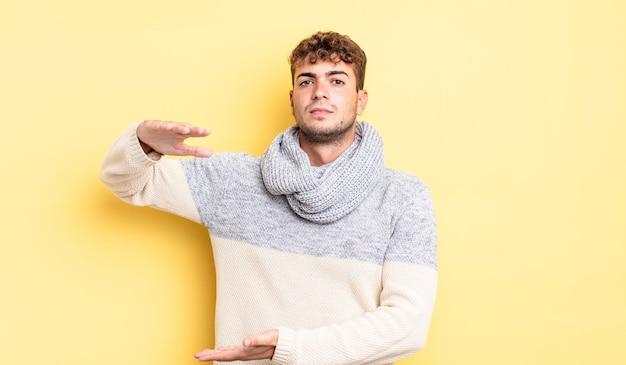 Jonge knappe man die een object vasthoudt met beide handen op de zijkopieerruimte, een object toont, aanbiedt of adverteert