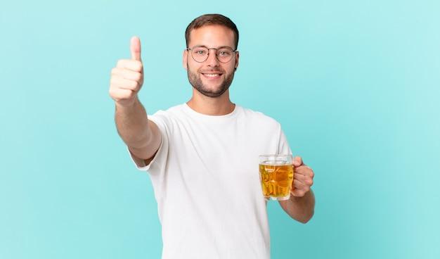 Jonge knappe man die een pint bier drinkt Premium Foto