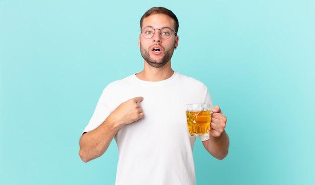 Jonge knappe man die een pint bier drinkt