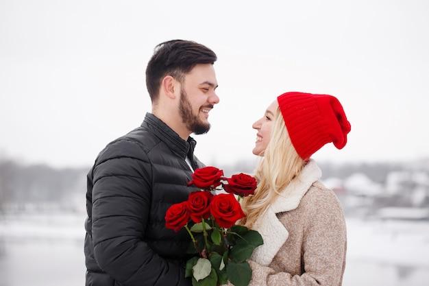Jonge knappe man die een vrouw een boeket rozen geeft op valentijnsdag