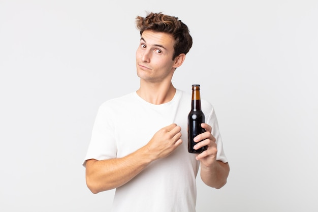 Jonge knappe man die er arrogant, succesvol, positief en trots uitziet en een bierflesje vasthoudt