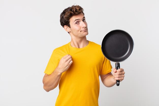 Jonge knappe man die er arrogant, succesvol, positief en trots uitziet en een kookpan vasthoudt