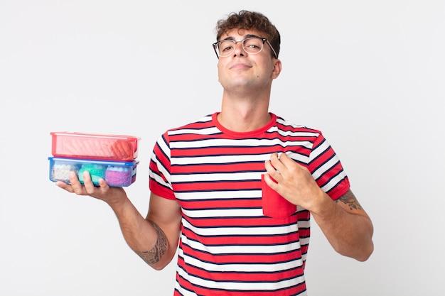 Jonge knappe man die er arrogant, succesvol, positief en trots uitziet en een lunchbox vasthoudt
