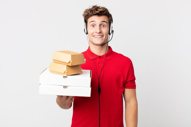 Jonge knappe man die er blij en aangenaam verrast uitziet. afhaal fastfood concept