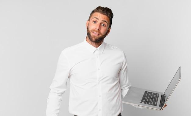 Jonge knappe man die er blij en aangenaam verrast uitziet en een laptop vasthoudt