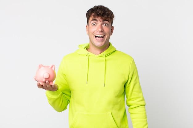 Jonge knappe man die er blij en aangenaam verrast uitziet en een spaarvarken vasthoudt