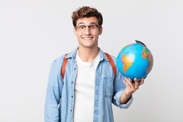 Jonge knappe man die er blij en aangenaam verrast uitziet. student met een wereldbolkaart