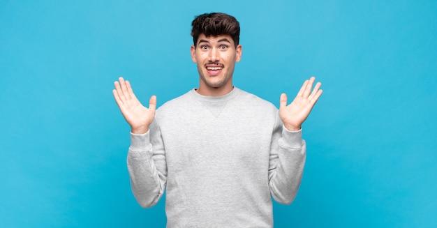 Jonge knappe man die er blij en opgewonden uitziet, geschokt door een onverwachte verrassing met beide handen open naast het gezicht