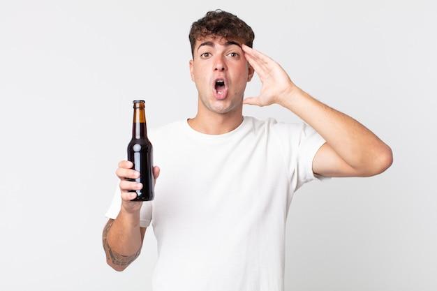 Jonge knappe man die er blij, verbaasd en verrast uitziet en een bierfles vasthoudt