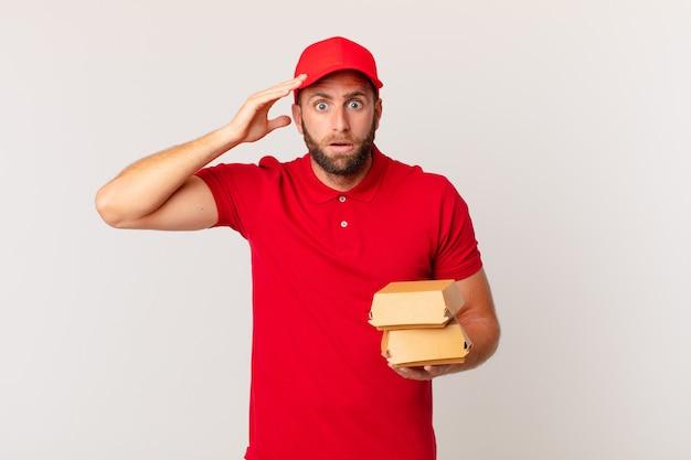 Jonge knappe man die er blij, verbaasd en verrast uitziet hamburger die concept levert