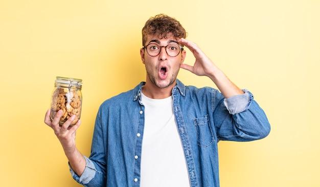 Jonge knappe man die er blij, verbaasd en verrast uitziet. koekjes fles concept