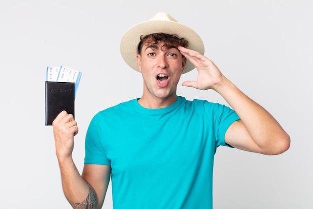 Jonge knappe man die er blij, verbaasd en verrast uitziet. reiziger met zijn paspoort