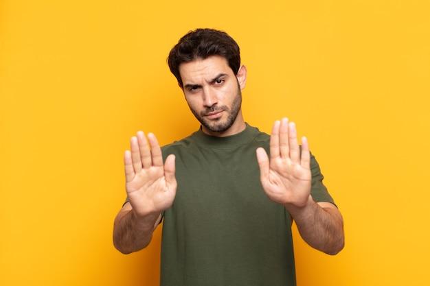 Jonge knappe man die er ernstig, ongelukkig, boos en ontevreden uitziet en de toegang verbiedt of stop zegt met beide open handpalmen