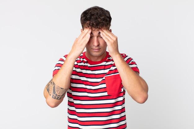 Jonge knappe man die er gestrest en gefrustreerd uitziet, onder druk werkt met hoofdpijn en last heeft van problemen