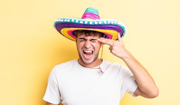 Jonge knappe man die er ongelukkig en gestrest uitziet, zelfmoordgebaar dat een pistoolteken maakt. mexicaanse hoed concept