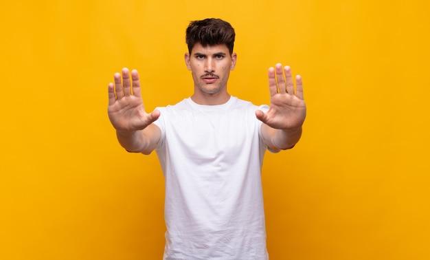Jonge knappe man die er serieus, ongelukkig, boos en ontevreden uitziet en de toegang verbiedt of stop zegt