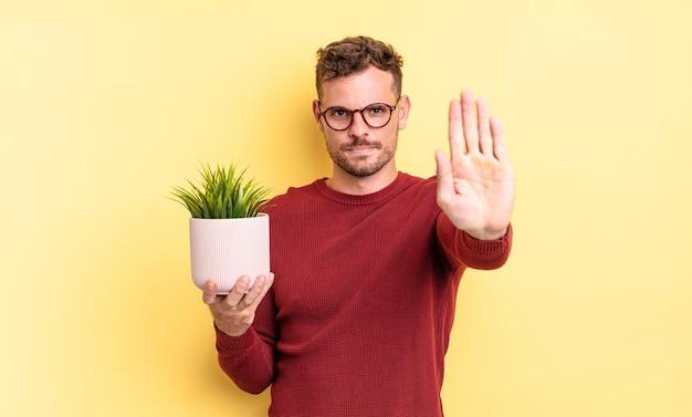 Jonge knappe man die er serieus uitziet en een open palm toont die een stopgebaar maakt. decoratief plantenconcept