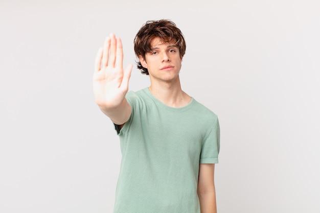Jonge knappe man die er serieus uitziet en een open palm toont die een stopgebaar maakt