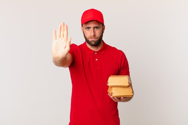 Jonge knappe man die er serieus uitziet en open palm laat zien die een stopgebaar maakt, hamburger die concept levert