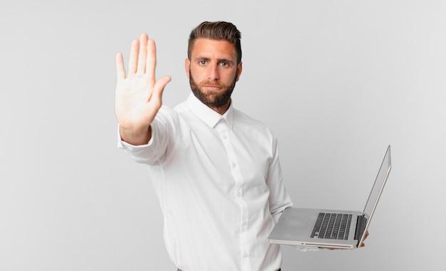Jonge knappe man die er serieus uitziet met een open palm die een stopgebaar maakt en een laptop vasthoudt