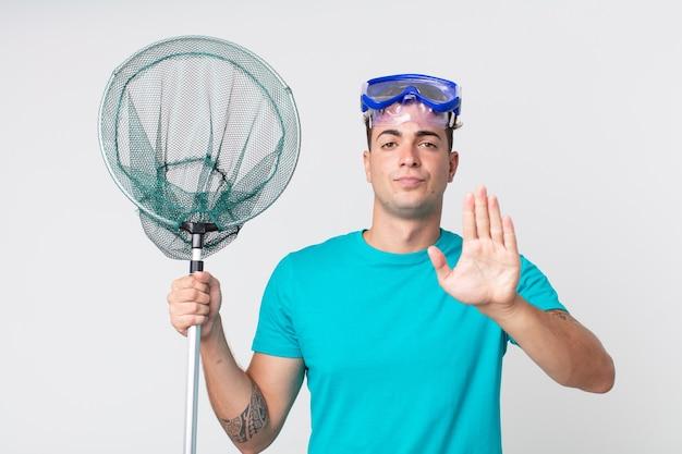 Jonge knappe man die er serieus uitziet met een open palm die een stopgebaar maakt met een bril en een visnet