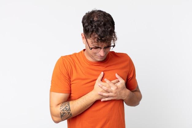 Jonge knappe man die er verdrietig, gekwetst en diepbedroefd uitziet, beide handen dicht bij het hart houdt, huilt en zich depressief voelt