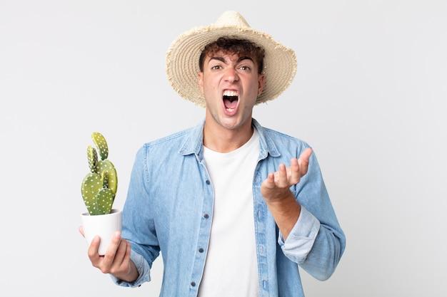 Jonge knappe man die er wanhopig, gefrustreerd en gestrest uitziet. boer met een decoratieve cactus