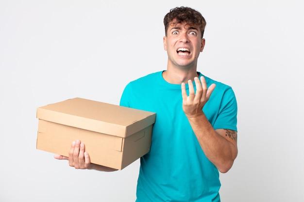 Jonge knappe man die er wanhopig, gefrustreerd en gestrest uitziet en een kartonnen doos vasthoudt