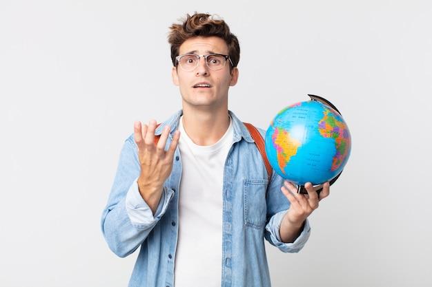 Jonge knappe man die er wanhopig, gefrustreerd en gestrest uitziet. student met een wereldbolkaart
