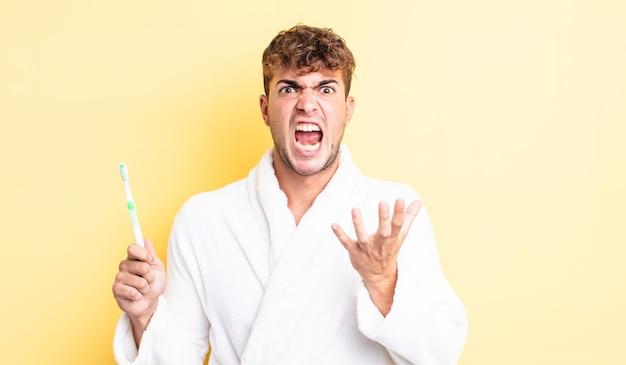 Jonge knappe man die er wanhopig, gefrustreerd en gestrest uitziet. tandenborstel concept