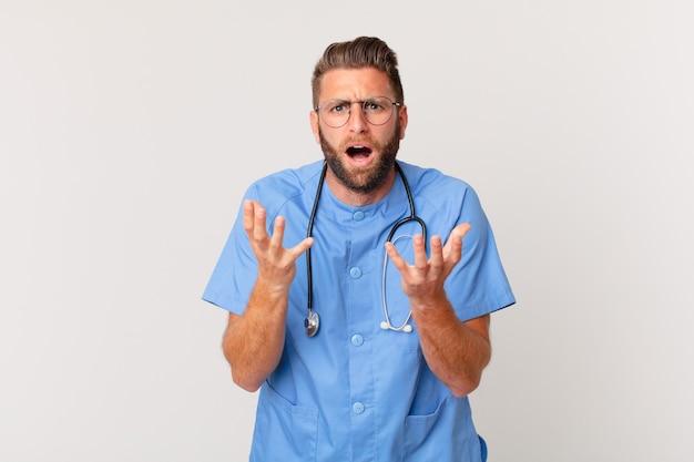 Jonge knappe man die er wanhopig, gefrustreerd en gestrest uitziet. verpleegster concept