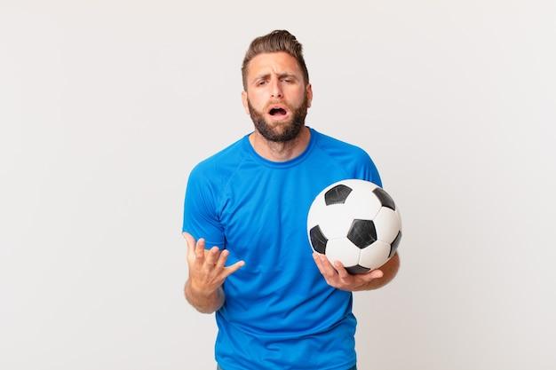 Jonge knappe man die er wanhopig, gefrustreerd en gestrest uitziet. voetbal concept