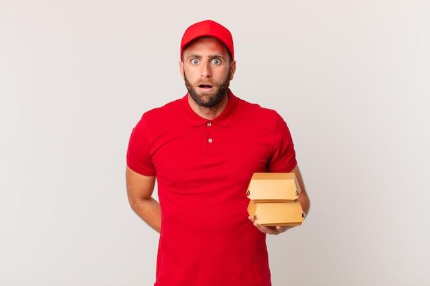 Jonge knappe man die erg geschokt of verrast hamburger levert concept