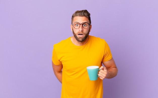 Jonge knappe man die erg geschokt of verrast kijkt. en een koffiemok vasthouden Premium Foto