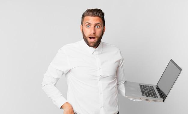 Jonge knappe man die erg geschokt of verrast kijkt en een laptop vasthoudt