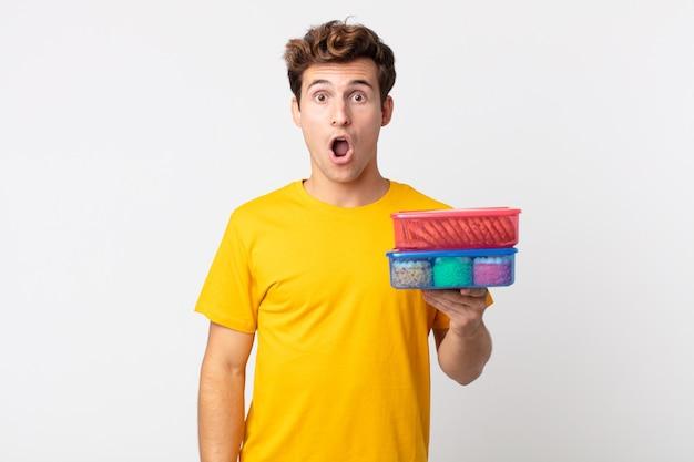 Jonge knappe man die erg geschokt of verrast kijkt en lunchboxen vasthoudt