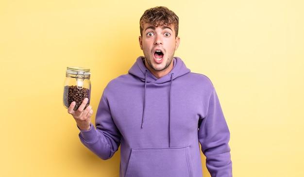 Jonge knappe man die erg geschokt of verrast kijkt. koffiebonen concept