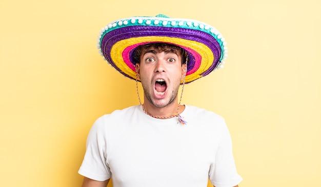 Jonge knappe man die erg geschokt of verrast kijkt. mexicaanse hoed concept
