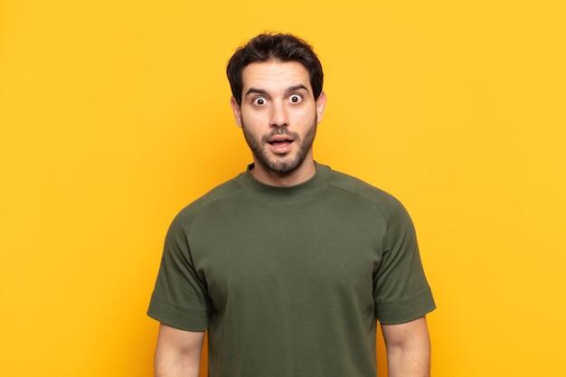 Jonge knappe man die erg geschokt of verrast kijkt, starend met open mond en zegt wow