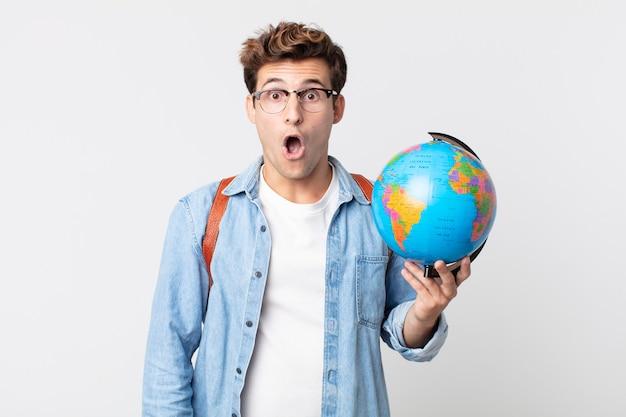 Jonge knappe man die erg geschokt of verrast kijkt. student met een wereldbolkaart