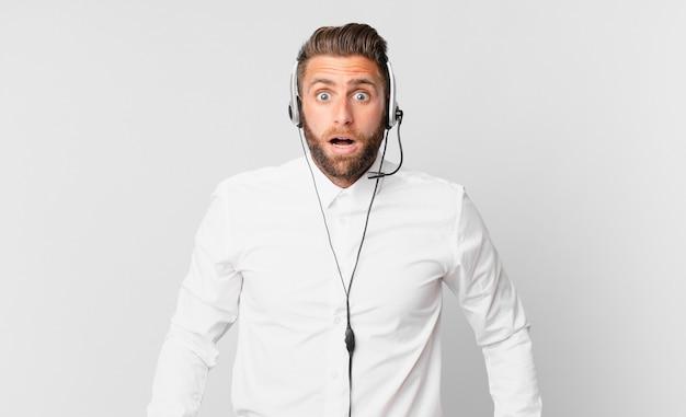 Jonge knappe man die erg geschokt of verrast kijkt. telemarketing concept