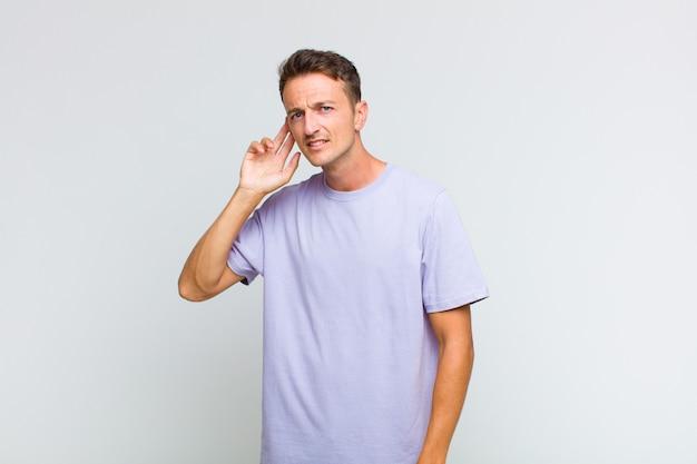 Jonge knappe man die ernstig en nieuwsgierig kijkt, luistert, probeert een geheim gesprek of roddel te horen, afluistert