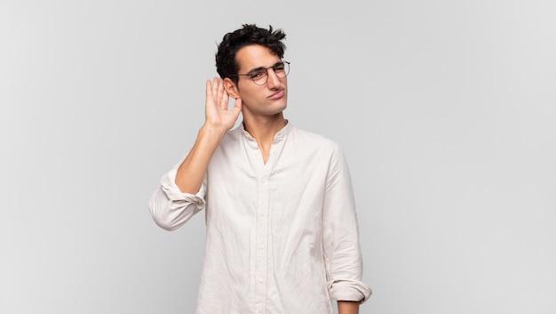 Jonge knappe man die ernstig en nieuwsgierig kijkt