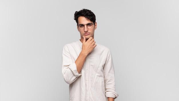 Jonge knappe man die ernstig, verward, onzeker en attent kijkt, twijfelt tussen opties of keuzes