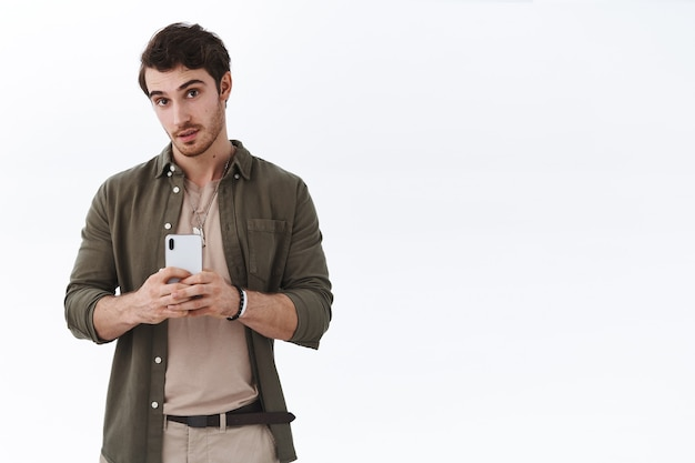 Jonge knappe man die foto maakt, smartphone vasthoudt
